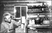 Photo - Interior view of shack with samples of tar sands and extractions, Fort McMurray, Alberta, 1920